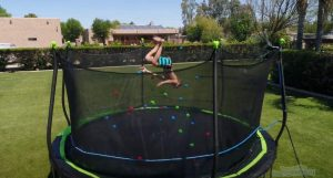 The kid is bouncing in the trampoline