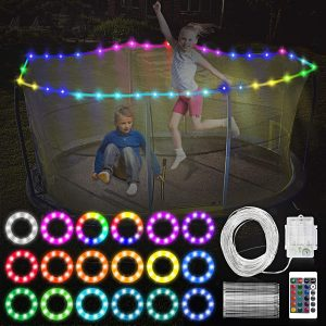 A boy and a girl playing together under the trampoline LED lights