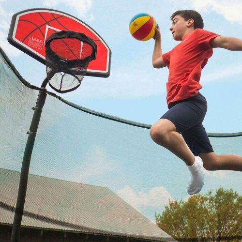 A boy in red shirt flying in the air to slam dunk the ball in the trampoline hoop