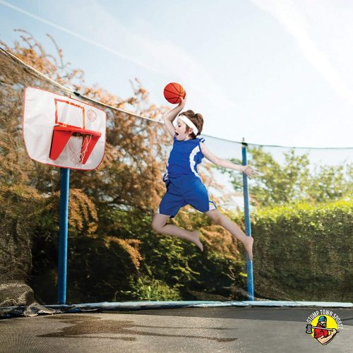 A boy jumping to slam dunk the basketball in trampoline