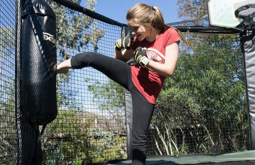 The girl kicking the training bag in the trampoline